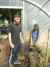 Student replanting plants in the community garden greenhouse (1L Yazel Sepulveda).